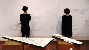 Instuctors facing a large wall-sized blueprint